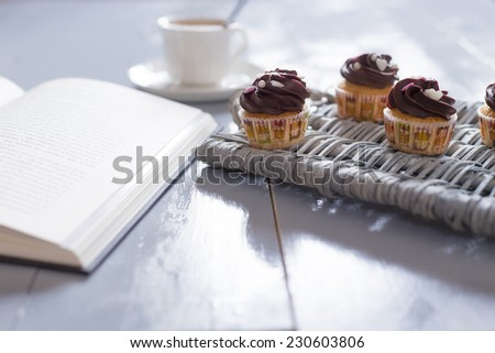 Reading is a pleasure. Four delicious chocolate cupcakes on a wicker tray with a hot cup of coffee and a open book on a blue rustic wood table - stock photo