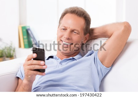 Reading new incoming messages. Cheerful mature man holding mobile phone and looking at it while sitting on the couch at home - stock photo