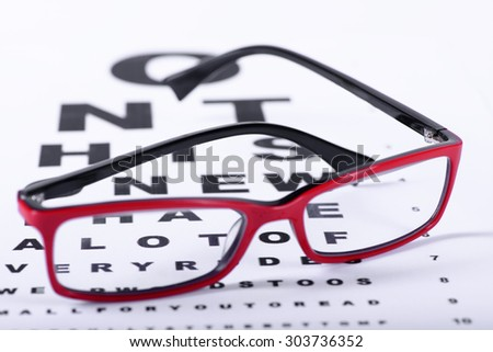 Reading red eyeglasses and eye chart close-up on a light background