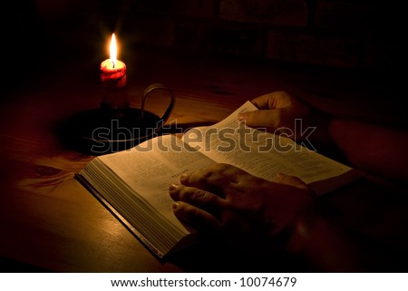 Reading the bible by candle light. Only light in this image is from the candle. Perfect for religious, eater or christmas themes. - stock photo
