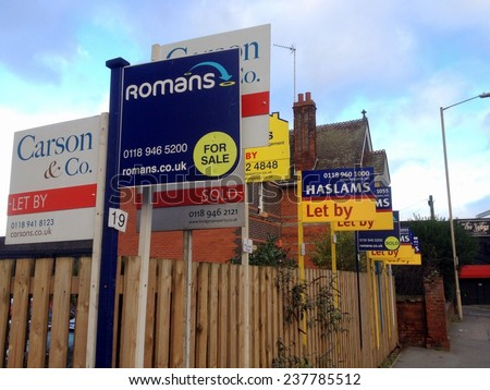 Reading, United Kingdom - December 11th, 2014: Estate Agency or Real Estate business advertising signs crowded together in a residential district of Reading, England on December 11th 2014 - stock photo