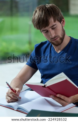 Reading young student with book on hand - stock photo