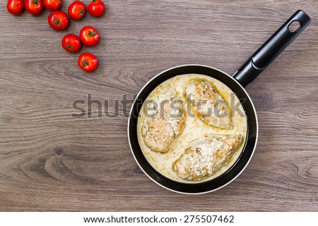 Ready chicken breast in a skillet with cream sauce. - stock photo