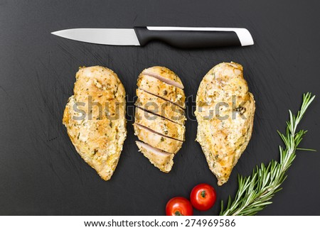 Ready chicken on the old plastic cutting board. - stock photo