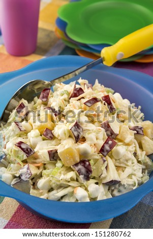 Ready for a summer picnic, a large bright bowl full of refreshing coleslaw is made with diced apples, marshmallows and pineapple chunks. - stock photo