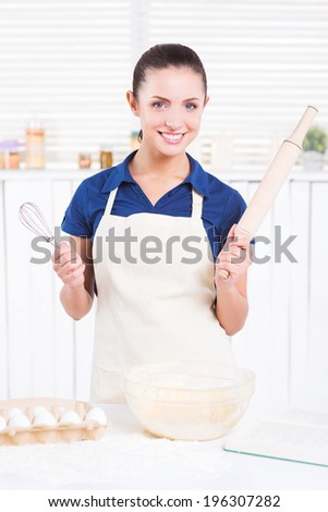 Ready for cooking. Cheerful young woman in apron holding rolling pin and wire whisk while standing in a kitchen - stock photo