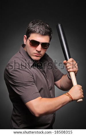 Ready for fight - Young man with a baseball bat isolated against black background - stock photo