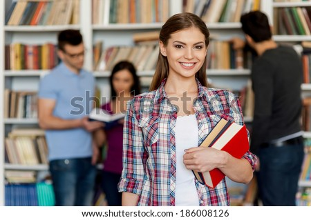 Ready for his final exam. Beautiful young woman holding books in her hand and smiling at camera while three other people standing behind her and near the bookshelf - stock photo
