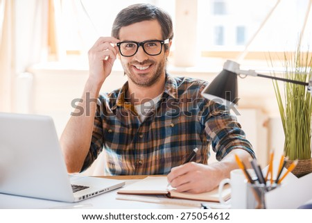 Ready for productive work. Smiling young man writing in note pad and adjusting his eyewear while sitting at his working place - stock photo