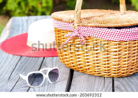 Ready for summer weekend. White sunglasses summer hat and wicker basket on wooden table outdoors. - stock photo