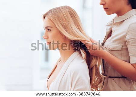 Ready for the shoot. Side view close-up of beautiful young woman looking away while hairstylist adjusting her hair in make-up room - stock photo