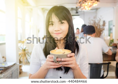 Ready for today image of beautiful woman with coffee cup in coffee shop white room sun beam