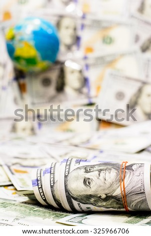 Ready for travel around the world with  American dollars currency,money ,Focus on roll of one hundred dollars and blurry background,globe - stock photo