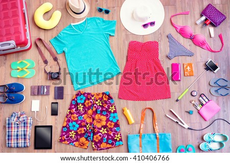 Ready for travel. Overhead of essentials for vacation. Top view of male and female summer accessories, clothes and gadgets on the wooden background. Packing suitcase. - stock photo
