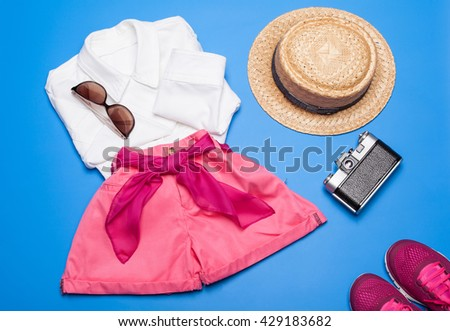 Ready for vacation! Collection of summer woman clothes and accessories on blue background - stock photo