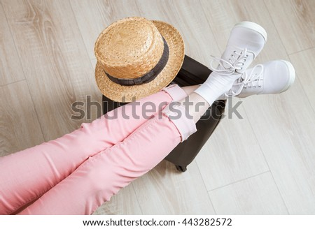 Ready for vacation! Unrecognizable traveler sitting in a relaxed pose with her legs on a packed suitcase - upper viewpoint - stock photo