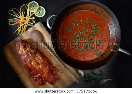 Ready scorpionfish sauce to garnish fettucine pasta, prepared by a typical Italian recipe. Overhead shot of the pan with sauce sprinkled with chopped fresh parsley and prepared scorpionfish on board. - stock photo