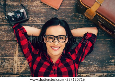 Ready to a big trip. Top view of beautiful young woman in eyewear lying on the hardwood floor and smiling while suitcase and camera laying near her  - stock photo