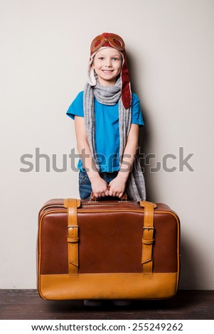 Ready to big travel. Happy little boy in pilot headwear and eyeglasses carrying a big briefcase and smiling