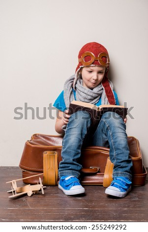 Ready to big travel. Happy little boy in pilot headwear and eyeglasses carrying a big briefcase and smiling  - stock photo