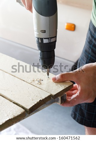 Ready to Drill Screw.  Man is about to continue to drill a screw into a plank of painted wood.  The drill is still. - stock photo