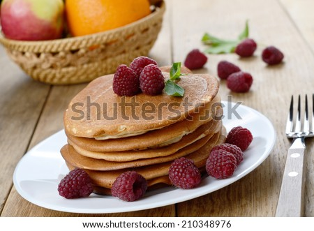 Ready to eat pancakes with raspberry on the white plate