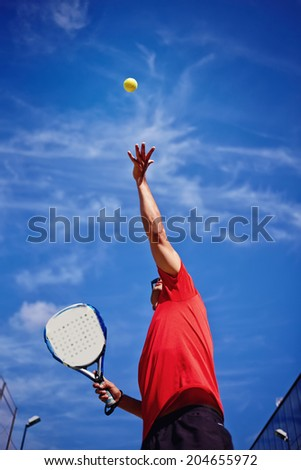 Ready to feed the ball in paddle game with beautiful athletic sportsman in bright t-shirt, paddle game outside, healthy lifestyle concept - stock photo
