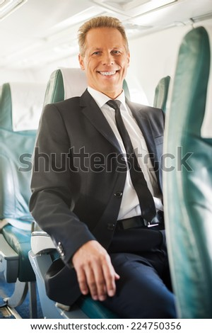 Ready to flight. Confident mature businessman sitting at his seat in airplane and smiling - stock photo