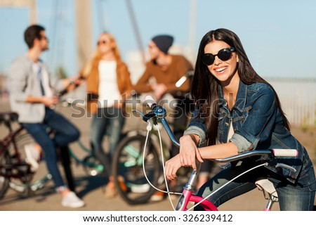 Ready to fun and adventures. Beautiful young smiling woman leaning at her bicycle and looking at camera while her friends talking in the background  - stock photo
