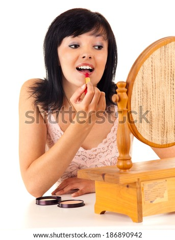 ready to go out, young lady applying lipstick, white background