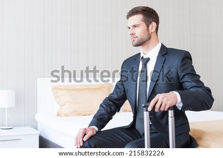 Ready to new business trip. Confident young businessman in formalwear carrying suitcase and smiling while sitting on the bed in hotel room  - stock photo
