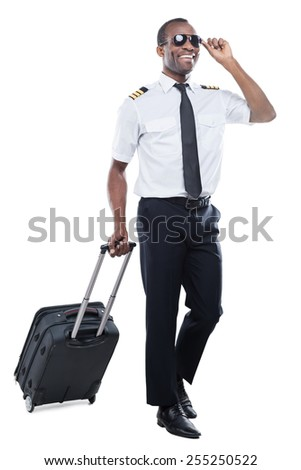 Ready to new flight. Happy African pilot in uniform walking and carrying suitcase while being isolated on white background - stock photo
