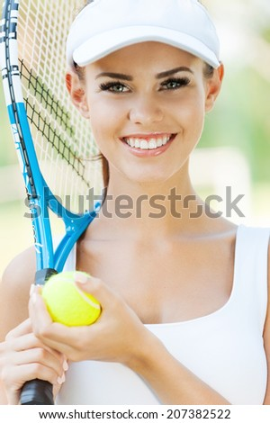 Ready to play? Beautiful young woman in sports clothing holding tennis racket and smiling - stock photo