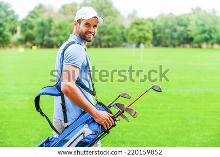 Ready to play. Rear view of young happy golfer carrying golf bag with drivers and looking over shoulder while standing on golf course - stock photo