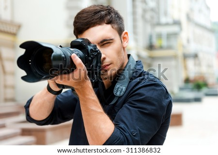Ready to shoot. Confident young man photographing something while standing outdoors - stock photo