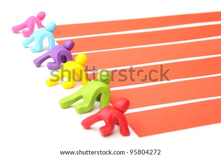 ready to start - six colorful plasticine athletes in front of race track waiting for the starting signal - stock photo