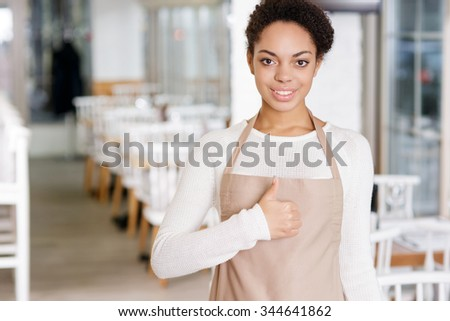 Ready to work. Attractive young waitress looking optimistic while showing thumbs up. - stock photo