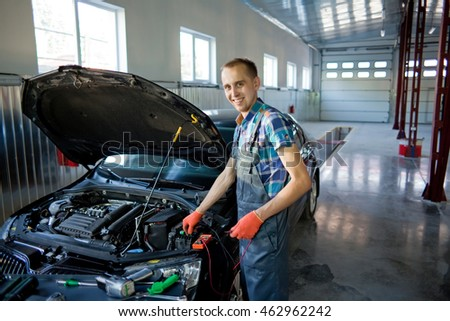 Real auto mechanic worker in garage.