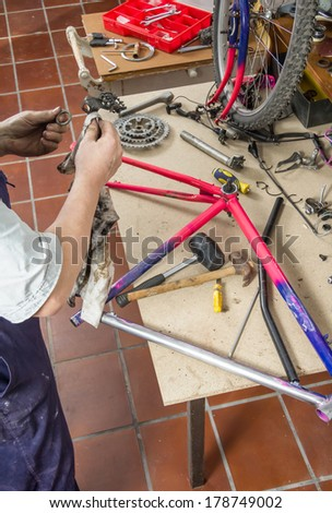 Real bicycle mechanic cleaning bike parts over workshop table in the repair process - stock photo
