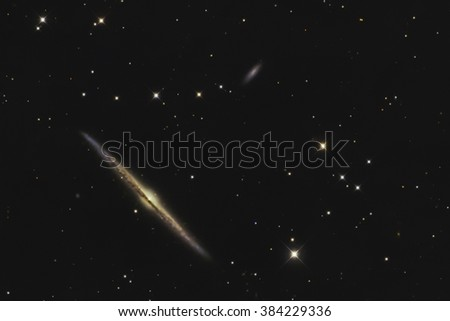 Real edge-on galaxy called needle galaxy or NGC4565 taken with CCD camera though medium size telescope - stock photo