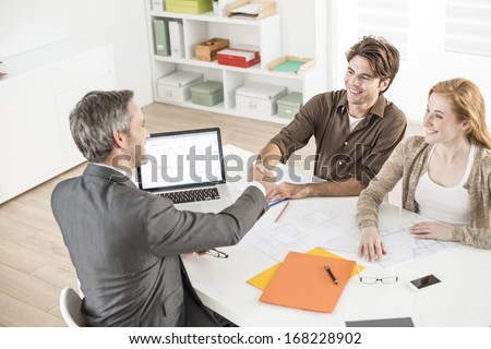 real-estate agent gives an handshake to a man in his office - stock photo