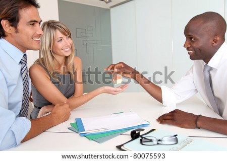 Real-estate agent giving house keys to new owners - stock photo