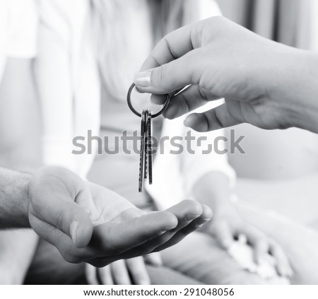 Real estate agent giving keys to young couple, closeup - stock photo