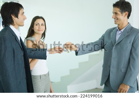 Real estate agent handing keys to young couple - stock photo