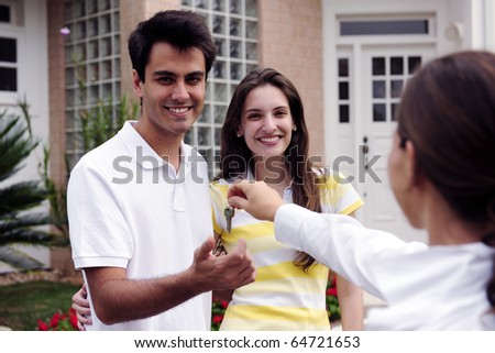 Real estate agent handing over house key to a happy couple - stock photo