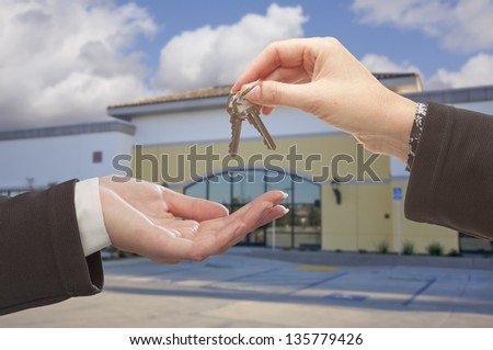 Real Estate Agent Handing Over the Keys in Front of Vacant Business Office. - stock photo