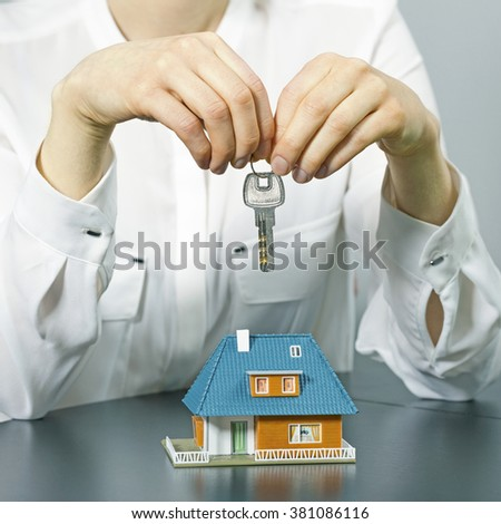 real estate agent holding key above small house model on the table. concept of buying new house - stock photo