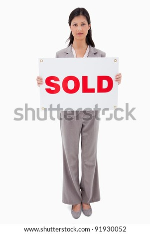 Real estate agent holding sold sign against a white background