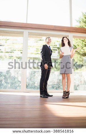 Real-estate agent interacting with young woman showing new home - stock photo