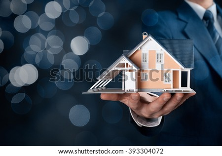 Real estate agent offer house represented by model. Insurance agent offer real estate insurance, bokeh in background. - stock photo